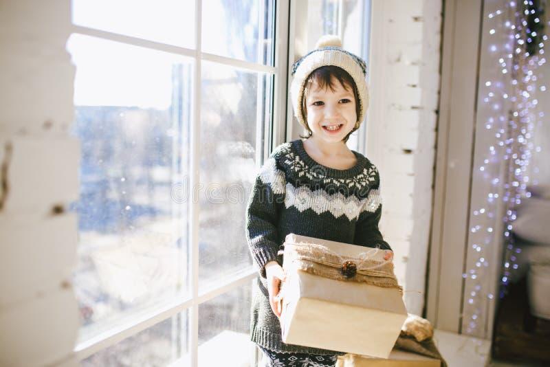 Het kind zit door het venster op een zonnige die Kerstmisdag en maakt met giften in vakjes op in document worden verpakt gekleed  royalty-vrije stock foto's