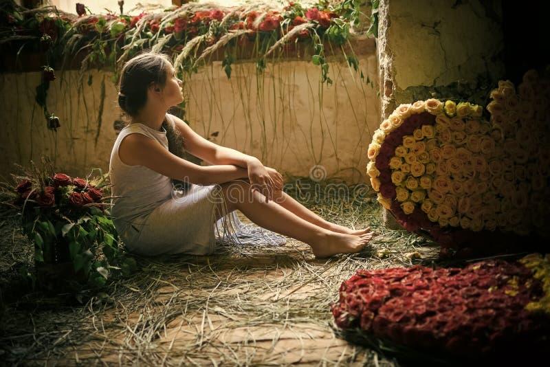 Het kind zit met bloemboeketten, bloemenregeling, slingers op vloer royalty-vrije stock afbeeldingen
