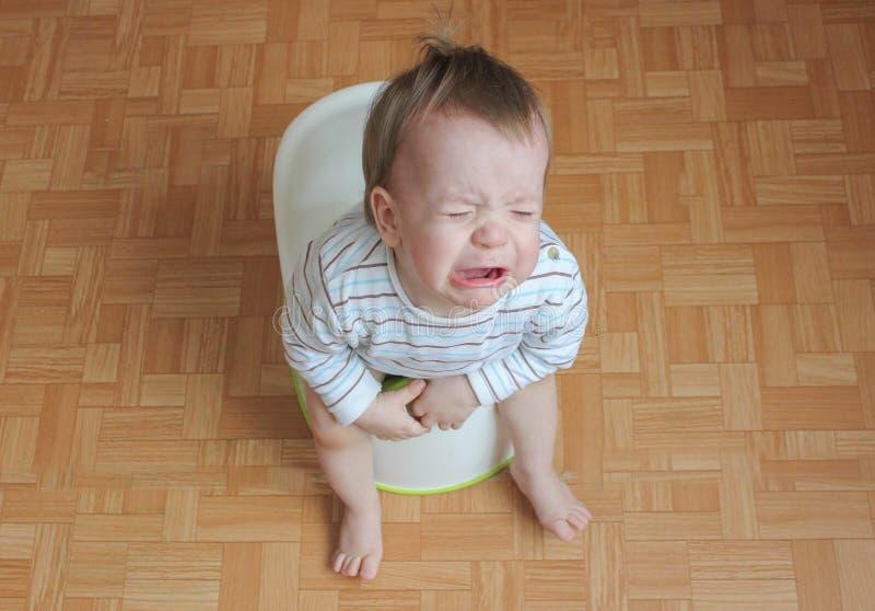 Het kind zit op een pot en schreeuwen Een kleine jongen wil niet aan royalty-vrije stock afbeeldingen