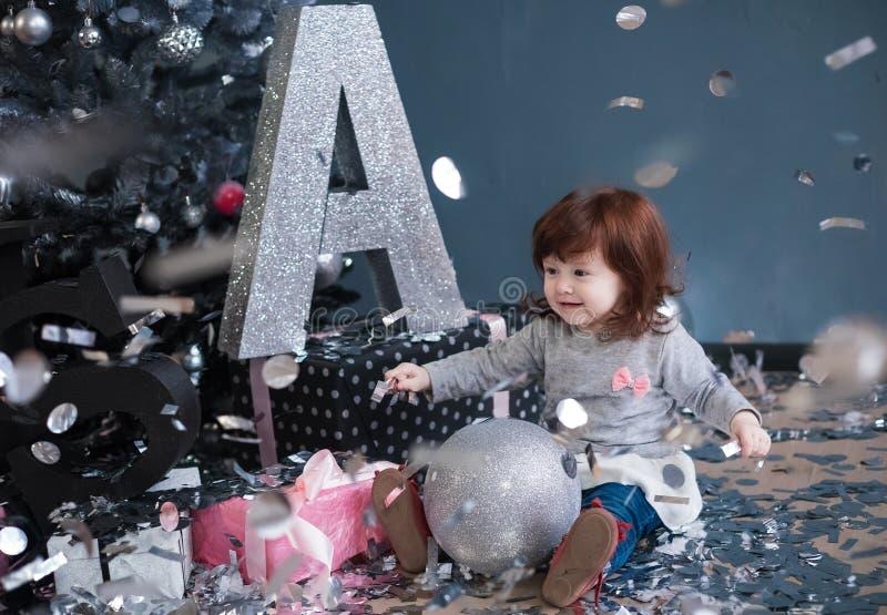Het kind zit op een vloer en houdt een grote Kerstmisbal Het kleine roodharige meisje stock afbeeldingen