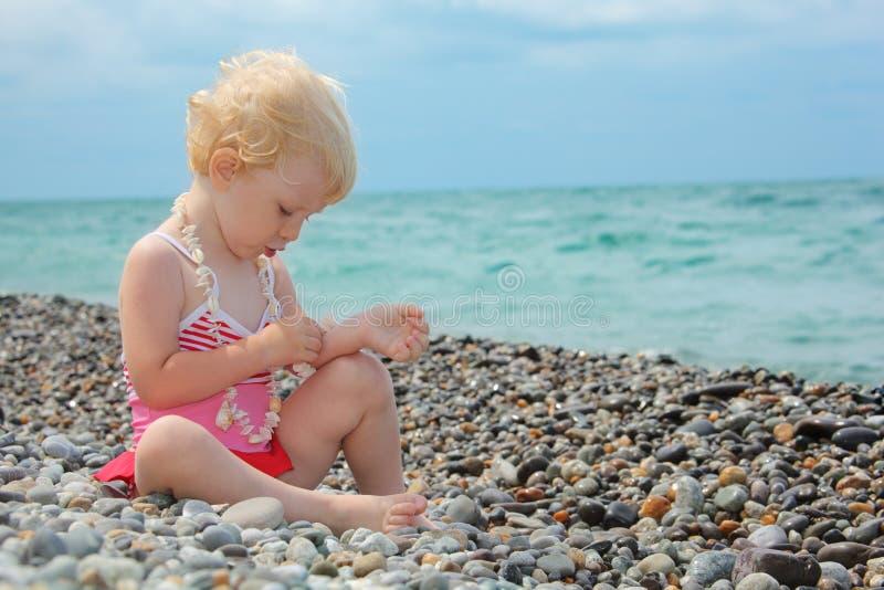 Het kind zit op kiezelsteenstrand royalty-vrije stock foto