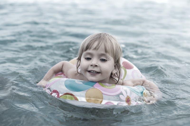 Het kind zwemt op een cirkel stock foto's