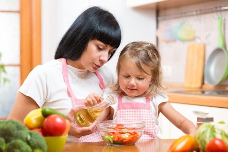 Het kinddochter die van het moederonderwijs salade in keuken maken Het koken concept gelukkige familie die voedsel voor diner voo royalty-vrije stock foto