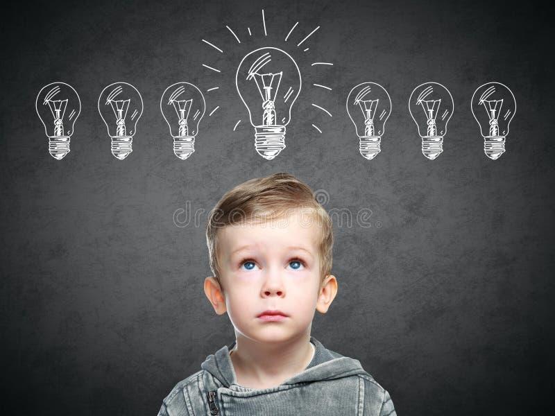Het kinderenidee met ontwerplamp, jongen kwam met idee op de proppen stock fotografie