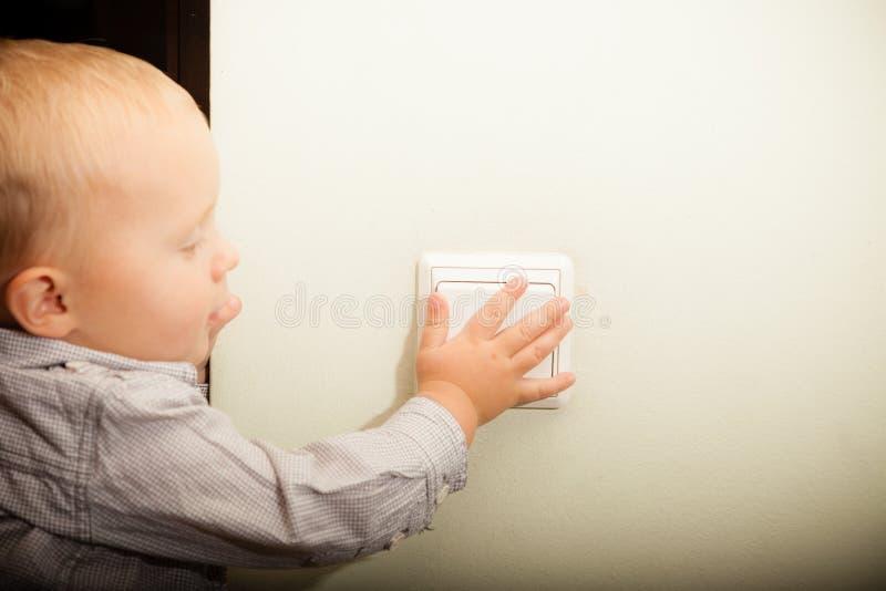 Het kindjong geitje die van de babyjongen het licht aanzetten stock afbeelding