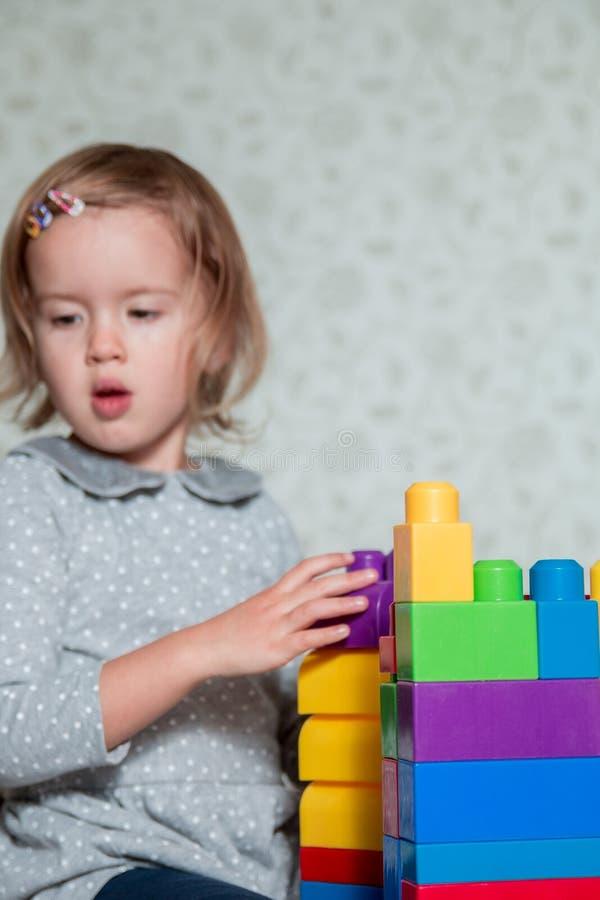 Het kindmeisje die pret hebben en bouwt stock foto's