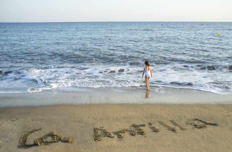Het kindmeisje geniet van bij Islantilla-overzeese kust Over het zand is bevelschrift stock afbeelding