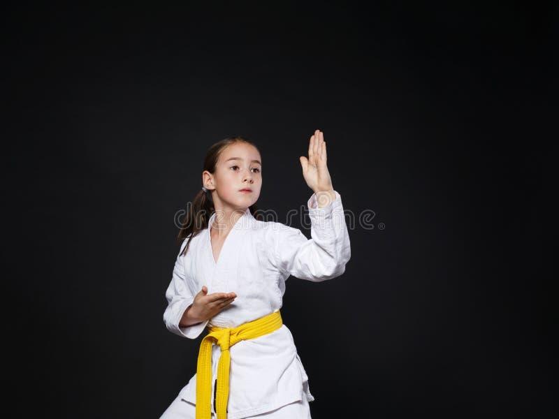 Het kindmeisje in karatekostuum met gele riem toont houding stock foto's