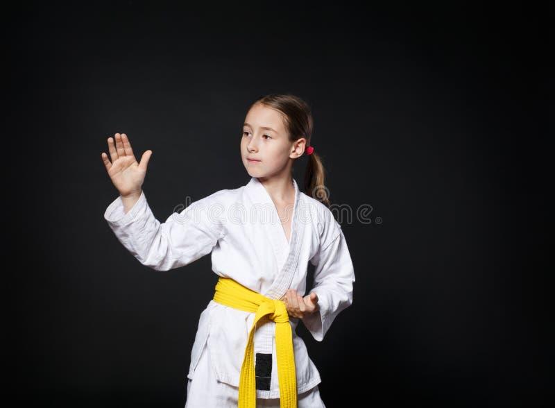 Het kindmeisje in karatekostuum met gele riem toont houding royalty-vrije stock foto's