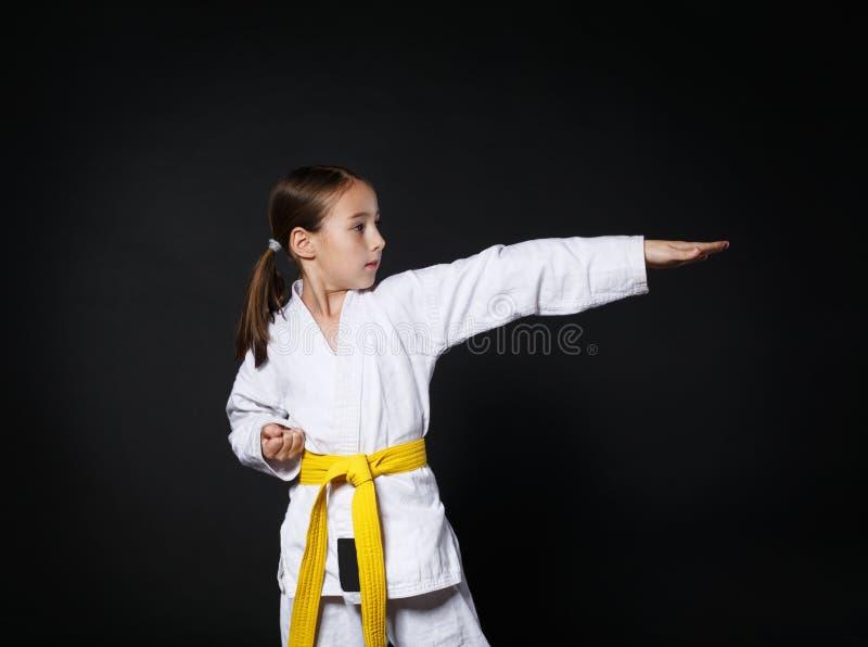 Het kindmeisje in karatekostuum met gele riem toont houding stock afbeeldingen
