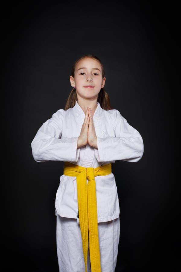 Het kindmeisje in karatekostuum met gele riem toont houding royalty-vrije stock fotografie