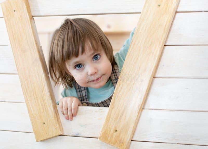 Het kindmeisje kijkt uit het venster van houten stuk speelgoed huis stock fotografie