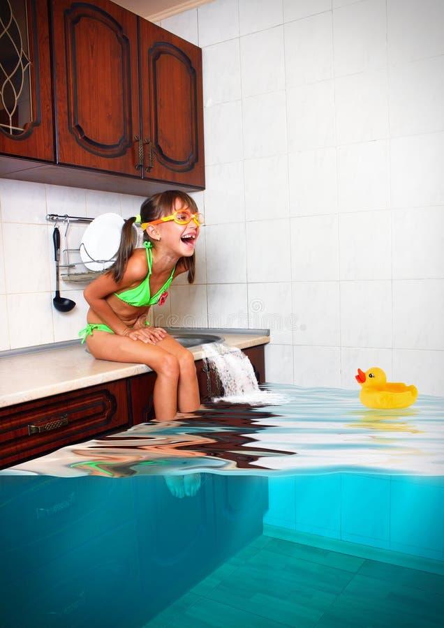 Het kindmeisje maakt knoeien, overstroomde keuken imiterend zwembad, F stock afbeeldingen