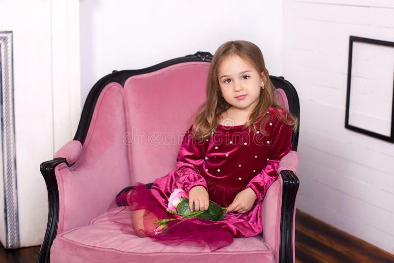 Het kindmeisje is mooi, leuk, vrolijk en gelukkig op een roze leunstoel in een modieuze luxueuze kleding Gelukkig kinderjarenconc royalty-vrije stock foto
