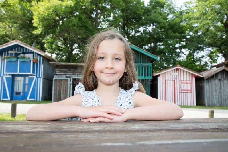 Het kindmeisje zit op bank houten lijst openlucht in de zomerdag in houten hutdorp in Biganos Arcachon in Frankrijk royalty-vrije stock fotografie