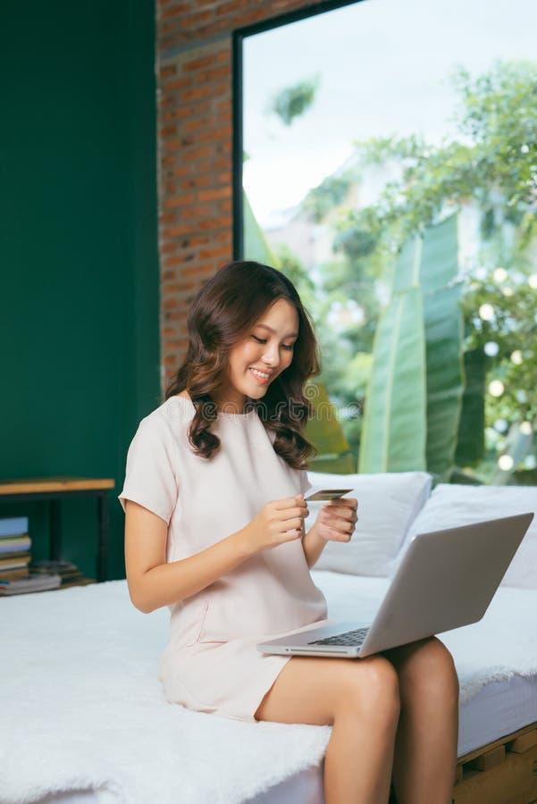 Het klantenmeisje koopt online met een laptop en creditcardzitting in aardige lichte ruimte royalty-vrije stock afbeelding