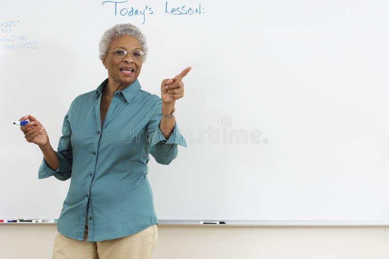 Het Klaslokaal van leraarsexplaining in the stock foto