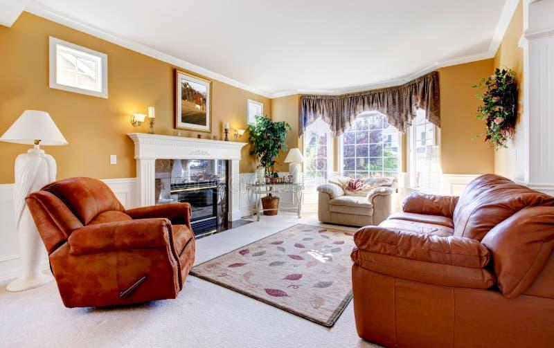 Het klassieke binnenland van de luxe comfortabele woonkamer met open haard en leer. royalty-vrije stock fotografie