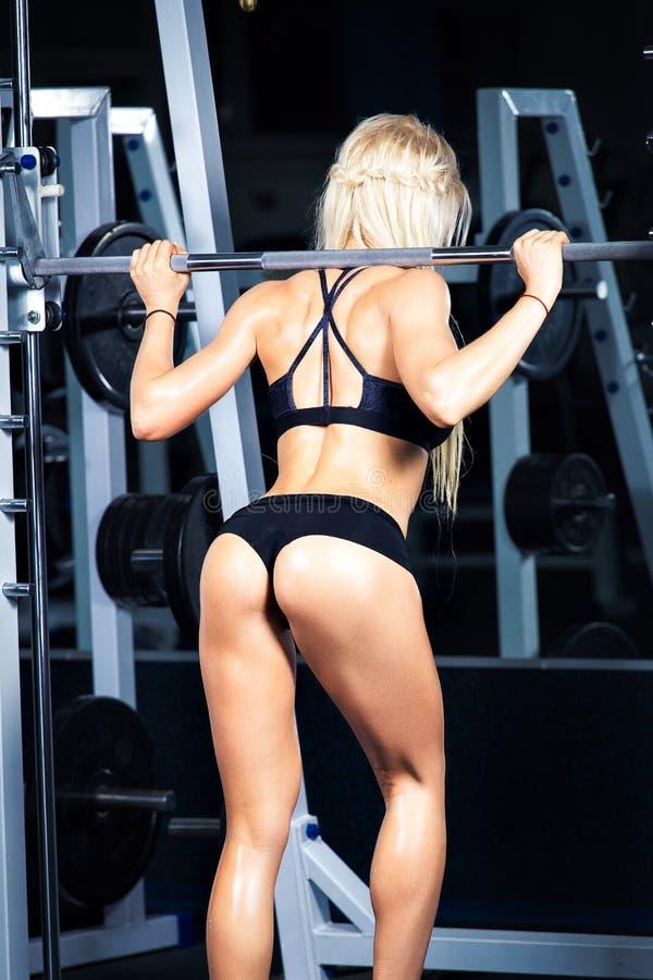 Het klassieke bodybuilding De spiervrouw die van de blondegeschiktheid oefeningen in de gymnastiek doen Geschiktheid - concept ge stock fotografie