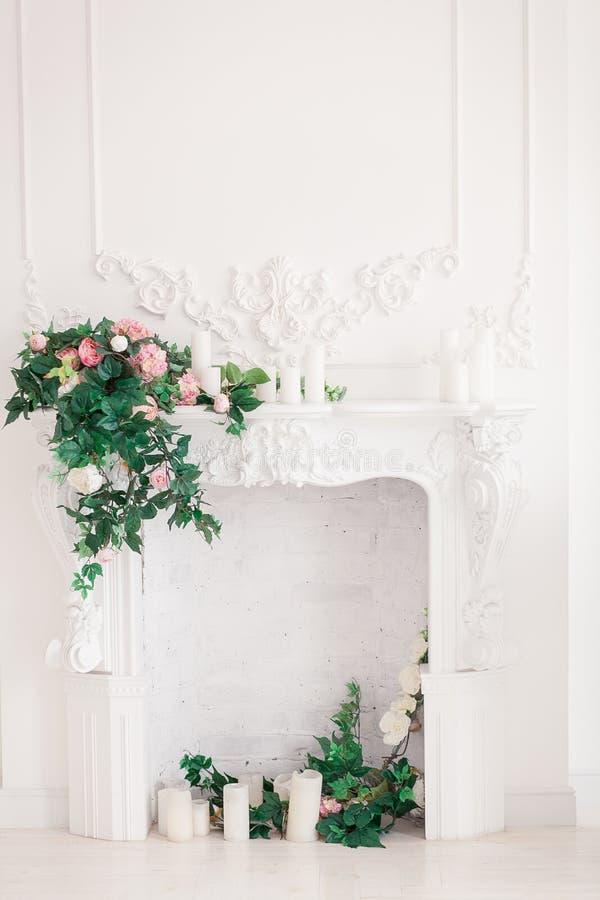 Het klassieke witte Binnenland van woonkamer met open haard en boeket van de lente bloeit op het stock fotografie