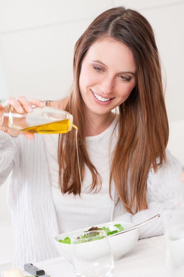 Het kleden van salade met olijfolie royalty-vrije stock foto's