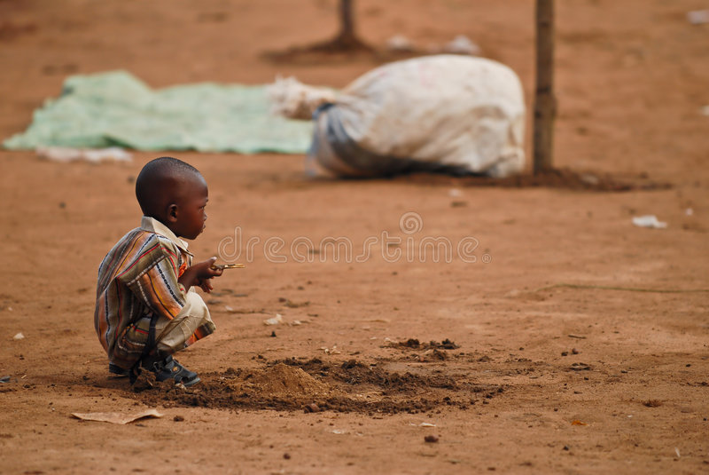 Het kleine Afrikaanse jongen hurken royalty-vrije stock fotografie