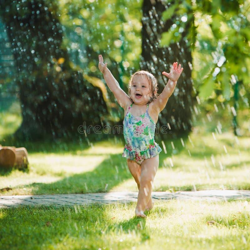 Het kleine babymeisje die met tuinsproeier spelen royalty-vrije stock foto