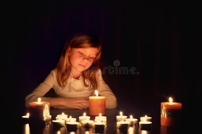 Het kleine blonde Kaukasische meisje kijkt op de kaarsen in dark royalty-vrije stock fotografie