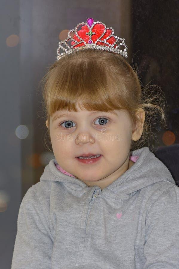 Het kleine blondemeisje met blauwe ogen stock fotografie