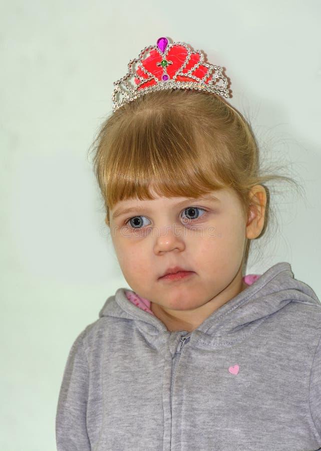 Het kleine blondemeisje met blauwe ogen stock foto