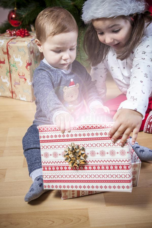 Het kleine broers hun openen stelt dicht bij Kerstboom voor stock fotografie