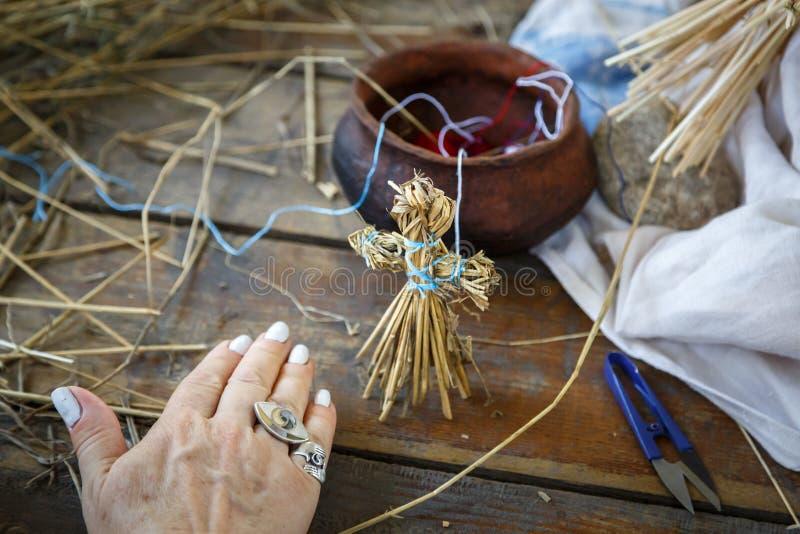 Het kleine die cijfer van een mens van stro wordt gemaakt, door de handen van een bejaarde wordt gemaakt bevindt zich op een hout stock fotografie