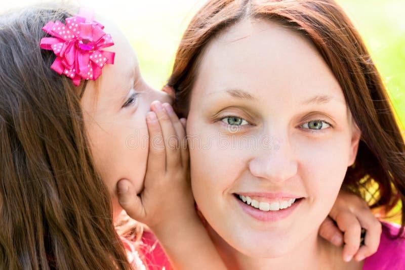 Het kleine geheime fluisteren in het oor van haar mama stock foto