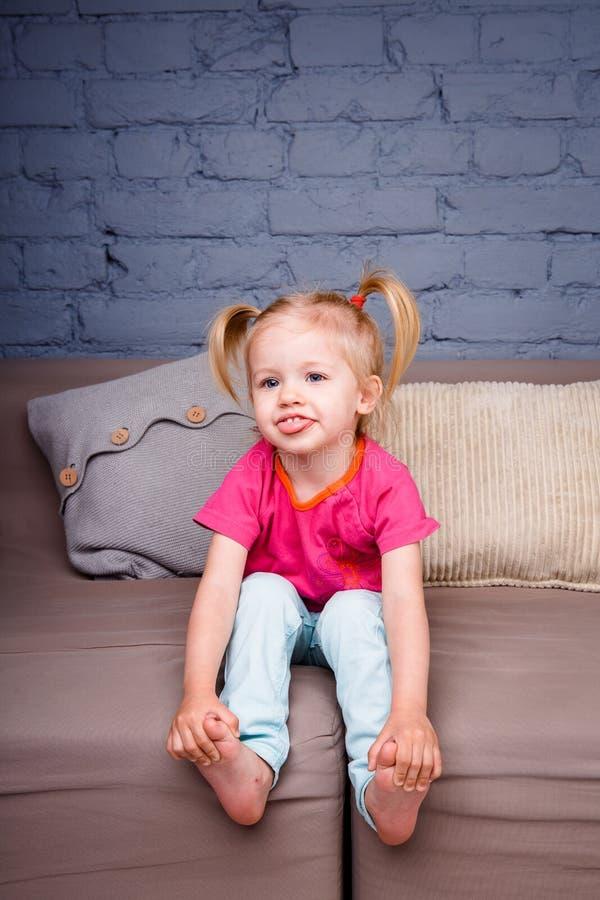 Het kleine grappige meisje stelt thuis op de bank met haar handen achter haar hielen tevreden Hij lacht tonend zijn tong en tande royalty-vrije stock afbeeldingen