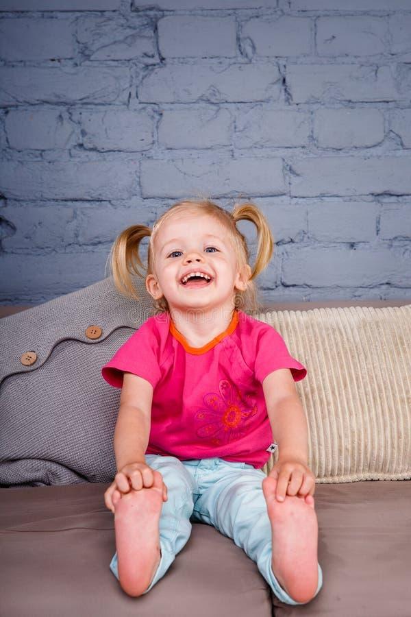 Het kleine grappige meisje stelt thuis op de bank met haar handen achter haar hielen tevreden Hij lacht tonend zijn tong en tande stock foto's