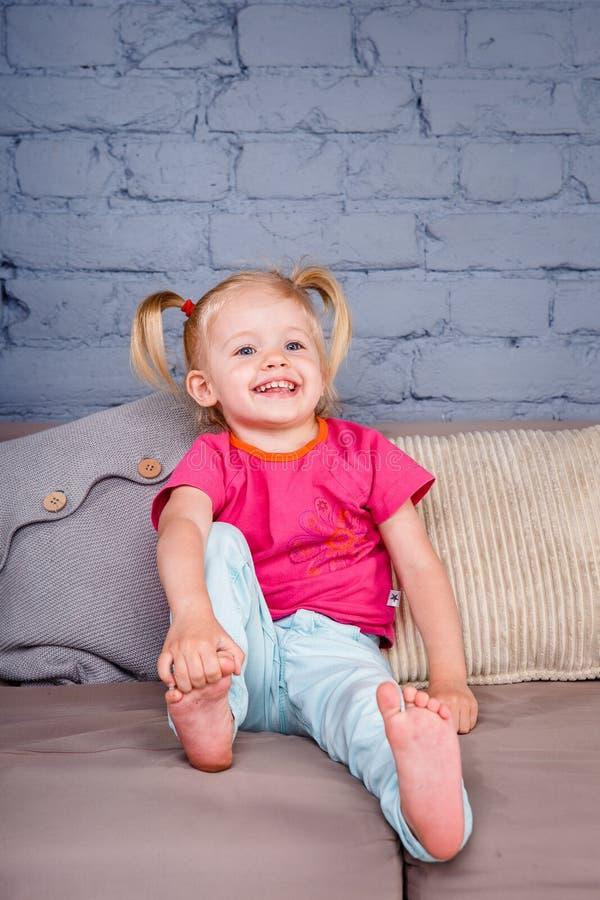 Het kleine grappige meisje stelt thuis op de bank met haar handen achter haar hielen tevreden Hij lacht tonend zijn tong en tande stock fotografie