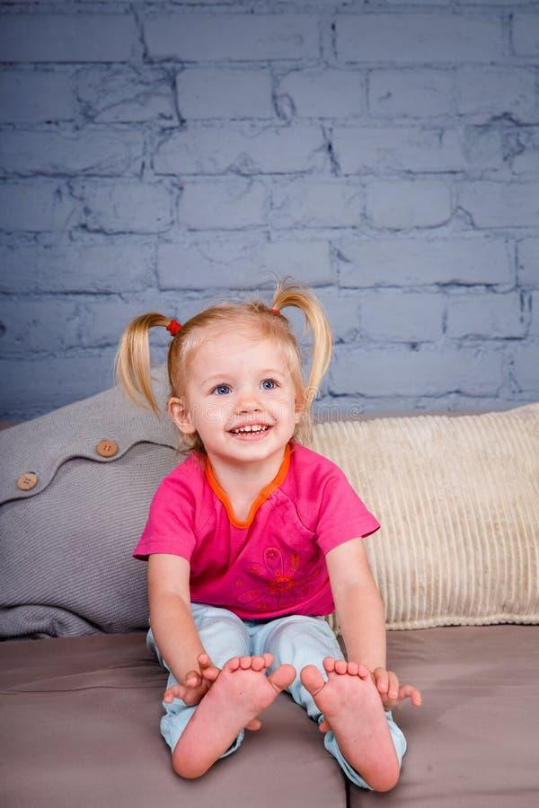 Het kleine grappige meisje stelt thuis op de bank met haar handen achter haar hielen tevreden Hij lacht tonend zijn tong en tande stock foto
