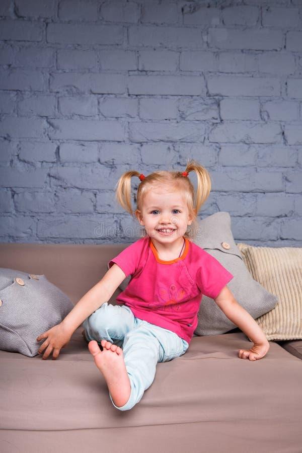 Het kleine grappige meisje stelt thuis op de bank met haar handen achter haar hielen tevreden Hij lacht tonend zijn tong en tande royalty-vrije stock foto