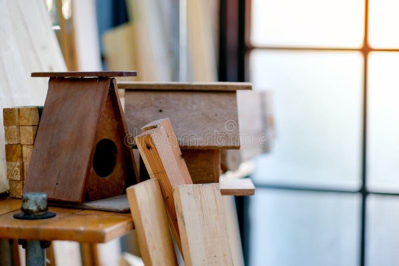 Het kleine houten huis of het nestkastje wordt gezet op de planken onder houten stapel en ander materiaal om in de ruimte te bewe stock fotografie