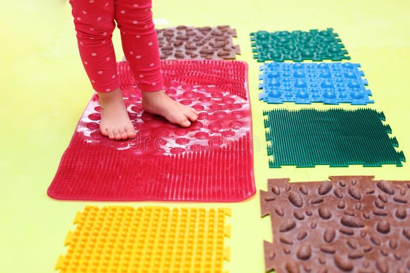 Het kleine kind met een platboomde maag gaat blootvoets op een orthopedische voetmat voor de benoeming van een orthopedistgymnast stock afbeelding