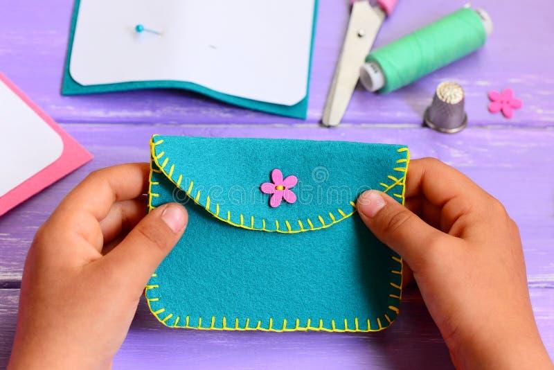 Het kleine kind naaide een beurs van gevoeld Het kleine kind houdt een beurs in zijn handen Eenvoudige met de hand gemaakte ambac royalty-vrije stock foto's