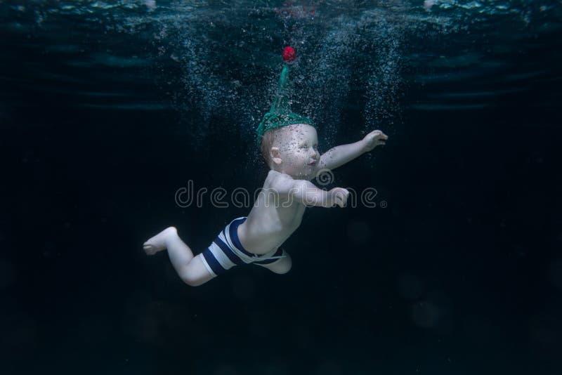 Het kleine kind is onder water stock foto