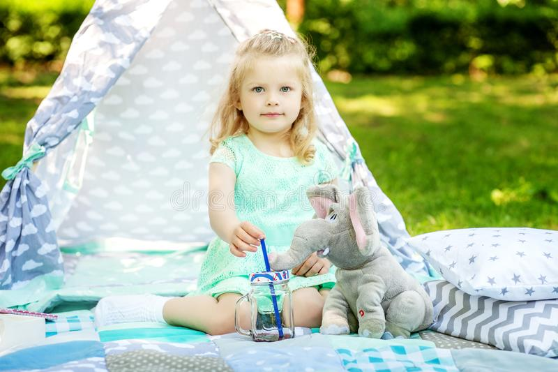 Het kleine kind spelen met een stuk speelgoed op een picknick Het concept lifes royalty-vrije stock afbeelding