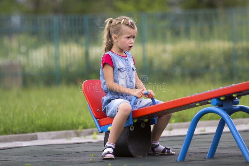 Het kleine leuke jonge blonde kindmeisje zit humeurig, boos en unsatisfied zie zaagschommeling op warme zonnige vage dag op helde royalty-vrije stock afbeelding