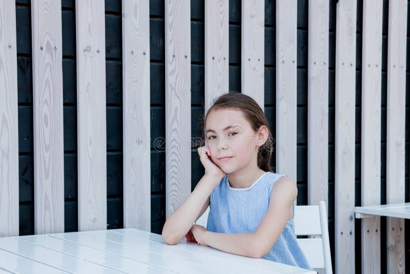 Het kleine leuke meisje zit bij de lege lijst van een straatkoffie stock foto