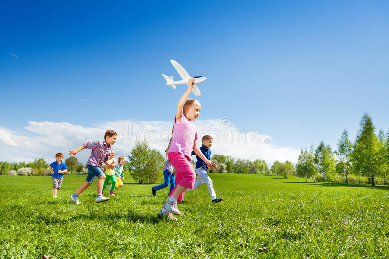 Het kleine meisje houdt vliegtuigstuk speelgoed en kinderen het lopen royalty-vrije stock afbeeldingen