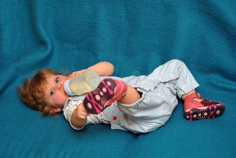 Download Het Kleine Meisje Liggen Op Blauwe Bank En Drinkt Melk Van Fles Stock Afbeelding - Afbeelding bestaande uit nieuwsgierig, pret: 29506009