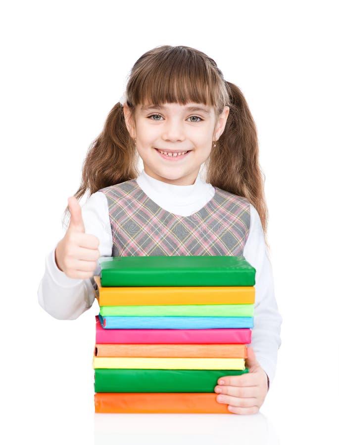 Het kleine meisje met stapelboeken het tonen beduimelt omhoog Geïsoleerd op wit royalty-vrije stock afbeelding