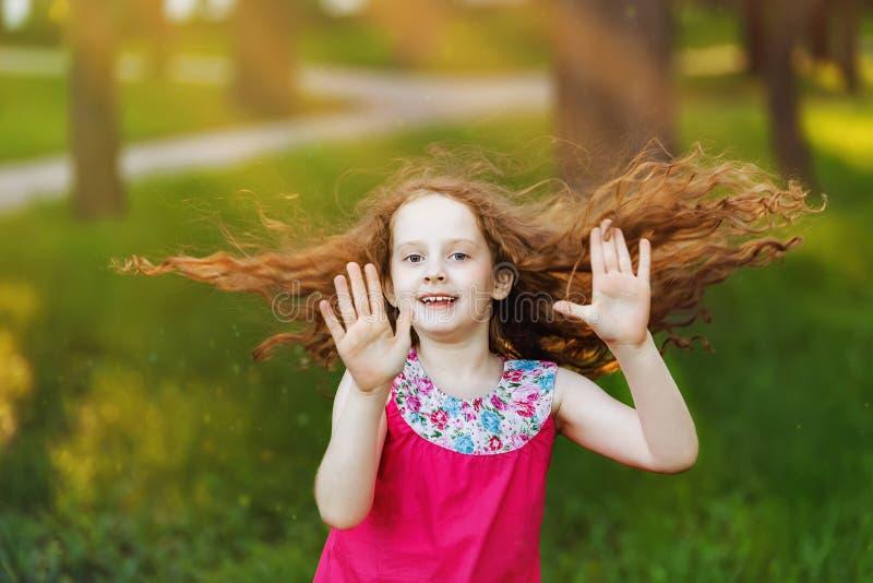 Het kleine meisje met vliegende haren danst in park royalty-vrije stock foto