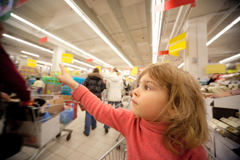 Het kleine meisje zit in shoppingcart in supermarkt stock afbeelding